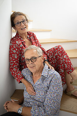Happy senior couple sitting on stairs - p1640m2254758 by Holly & John