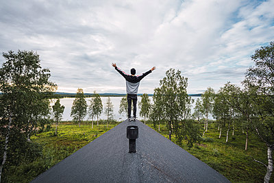 Finland, Lapland, man standing on roof of a house at a lake with raised arms - p300m2060808 by Kike Arnaiz