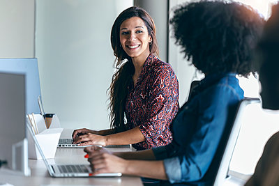 Smiling female professional looking at colleague while working on laptop in office - p300m2275573 by Josep Suria