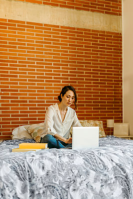 Woman using laptop while sitting on bed at home - p300m2277669 by Valentina Barreto
