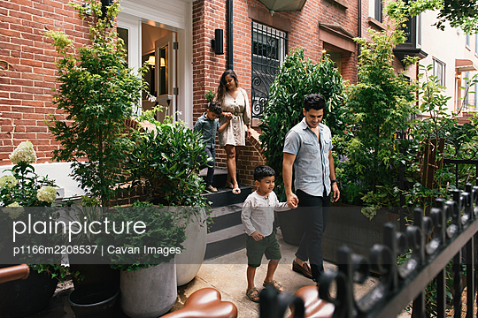 Young wealthy family walking out from there luxurious brownstone home - p1166m2208537 by Cavan Images