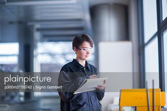 Female technician at work taking notes - p300m2155742 von Sigrid Gombert