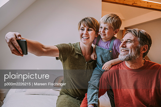 Happy mother taking selfie on smart phone while father and son sitting beside at home - p300m2226215 by Mareen Fischinger