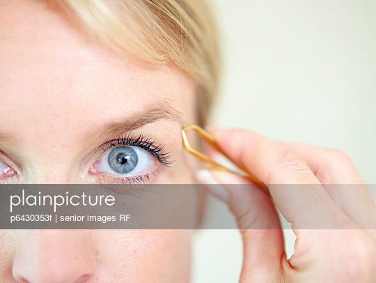 Aeltere Frau beim Augenbrauenzupfen  - p6430353f von senior images RF