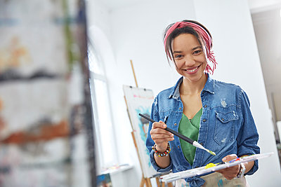 Portrait smiling female artist with paintbrush and palette, painting in art class studio - p1023m1506492 by Agnieszka Olek