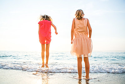 Two girls jumping in the waves - p1113m1215023 by Colas Declercq