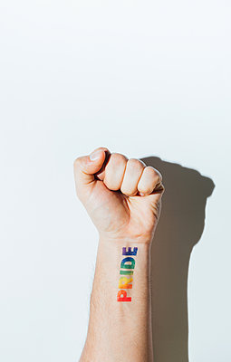 Gay guy's hand with a tattoo that says pride and nail polish. - p1166m2191816 by Cavan Images