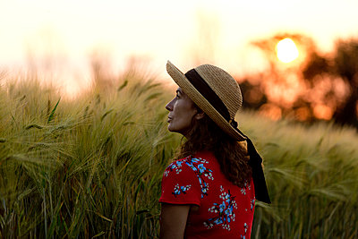 Woman in front of grain field wearing straw hat and red summer dress with floral design at sunset - p300m2119705 by FL photography