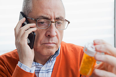 Serious Hispanic man talking on cell phone holding prescription bottle - p555m1301691 by REB Images