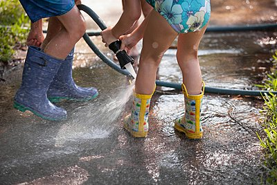 Children playing with water hose on sidewalk - p924m1125722f by Kinzie Riehm
