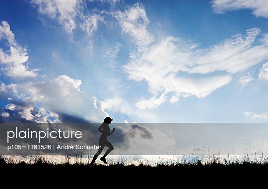 Läuferin als Silhouette vor bewölktem Himmel - p105m1181526 von André Schuster