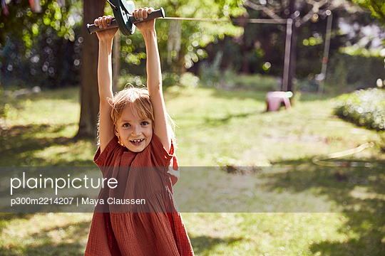 Cheerful girl hanging on outdoors play equipment in yard - p300m2214207 by Maya Claussen