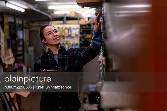 Female mechanic with digital tablet touching machinery at workshop - p300m2290586 by Kniel Synnatzschke