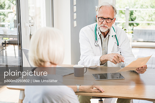 Male doctor holding medical report while looking at female patient at desk - p300m2293802 by Uwe Umstätter