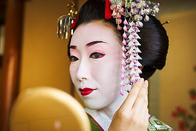 A woman made up in the traditional geisha style, with an elaborate hairstyle and floral hair clips, with white face makeup with bright red lips and dark eyes. Looking in a hand mirror.  - p1100m1185713 by Mint Images