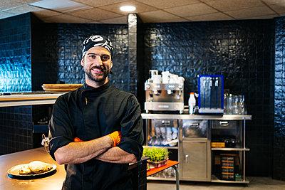 Portrait of smiling chef in restaurant kitchen - p300m2166749 by Daniel González
