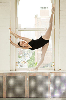 Ballerina stretching in window - p9245554f by Image Source