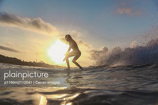Female surfer in ocean at sunset - p1166m2112041 by Cavan Images