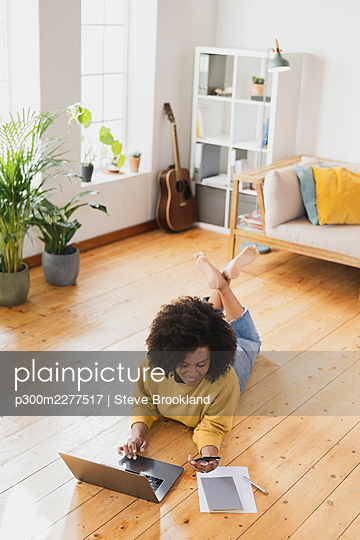Smiling woman using mobile phone while lying on floor by laptop at home - p300m2277517 by Steve Brookland