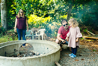 Straight on view of a family roasting marshmallows on a campfire - p1166m2131376 by Cavan Images
