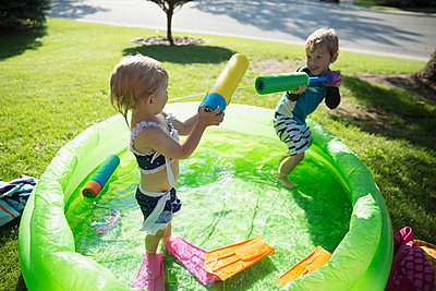 Brother and sister with squirt guns in sunny wading pool - p1192m1184003 by Hero Images