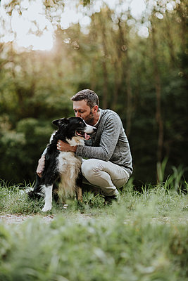 Man kissing his dog while crouching at park - p300m2226273 by Gala Martínez López