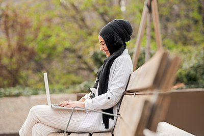 Smiling female entrepreneur working on laptop while sitting on bench outdoors - p300m2265898 by Jose Carlos Ichiro