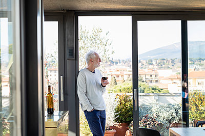 Senior man holding wineglass while leaning by sliding door at home - p300m2265899 by Emma Innocenti