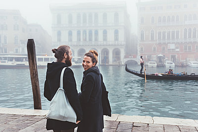 Rear view of couple on misty canal waterfront, Venice, Italy - p429m1408080 by Eugenio Marongiu