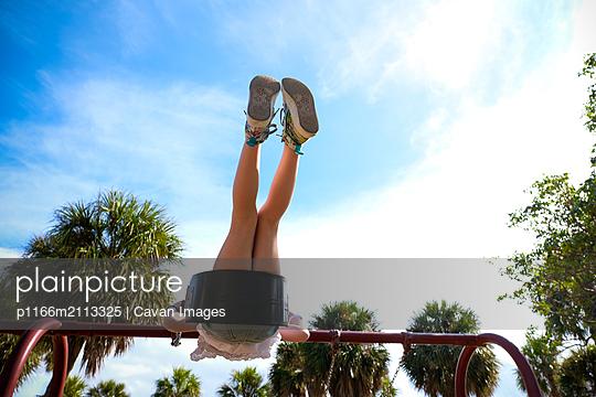 view from below of girl on swing legs in air against blue sky at park - p1166m2113325 by Cavan Images