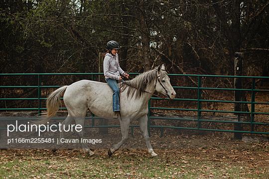 Teen girl in helmet riding horse bareback in round pen - p1166m2255481 by Cavan Images