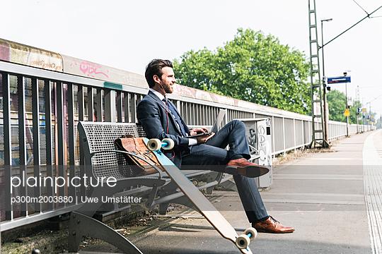 Smiling businessman with skateboard using laptop at the platform - p300m2003880 von Uwe Umstätter