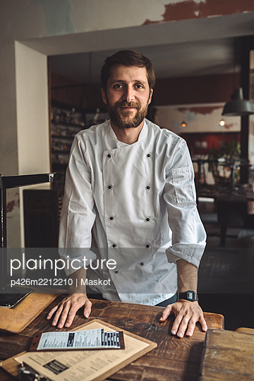 Portrait of confident chef standing by table in restaurant - p426m2212210 by Maskot
