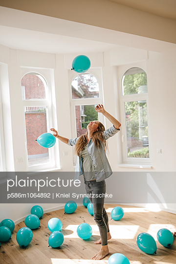 Young woman in new apartment playing with balloons - p586m1064892 by Kniel Synnatzschke