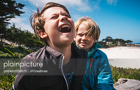 Two boys sitting by sandy beach near Carmel, California, USA, teasing each other. - p924m2208570 by JFCreatives