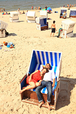 Couple in a hooded beach chair - p0452633 by Jasmin Sander