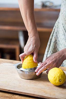 Woman squeezing lemon juice - p300m1204425 by Alberto Bogo