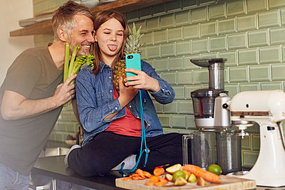 Happy father and daughter in kitchen making a selfie with fruit and vegetable - p300m2189327 by Maya Claussen