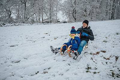 Father and son racing down a snowy slope with their sledge, Blankenheim, NRW, Germany - p300m2267739 von Mareen Fischinger