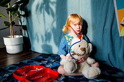 Aspiring blond girl playing with stethoscope and teddy bear at home - p300m2277262 by Irina Heß