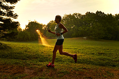 A woman running at sunrise. - p343m1203835 by Josh Campbell