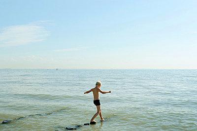 Boy walking on posts in ocean - p42918769 by Mischa Keijser
