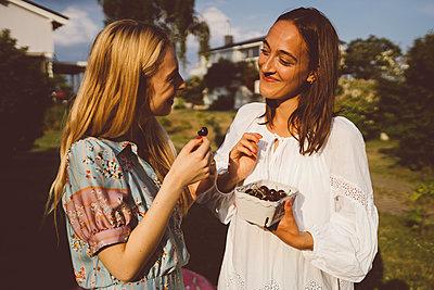 Beste Freundinnen essen Kirschen im Garten - p432m2260279 von mia takahara