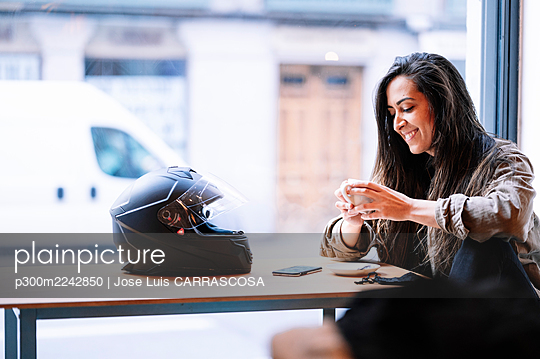 Smiling young woman with helmet having coffee in cafe by glass - p300m2242850 by Jose Luis CARRASCOSA
