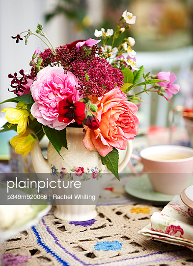 Cut flowers on crochet tablecloth with teacup in Isle of Wight home;  UK - p349m920066 by Rachel Whiting