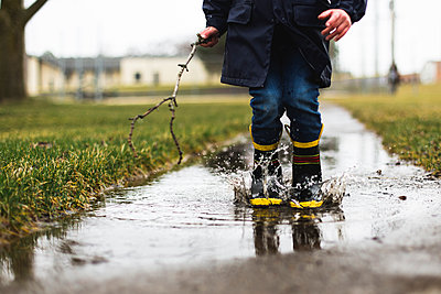 Low section of boy holding stick while jumping in puddle - p1166m1474036 by Cavan Images