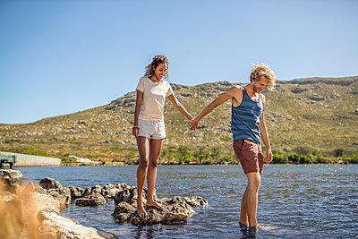 Junges Paar Hand in Hand am Flussufer - p1355m1574216 von Tomasrodriguez