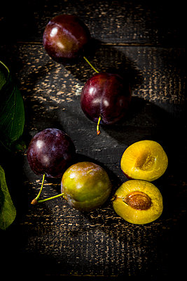 Whole and sliced plums on dark wood - p300m2023464 by Roman Märzinger