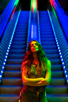 Portrait of illuminated young woman in front of blue lighted escalator - p300m2028723 by VITTA GALLERY