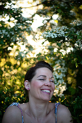Lauging woman in front of blooming hawthorn - p310m2289394 by Astrid Doerenbruch